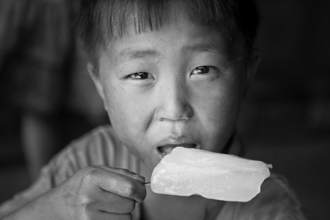 A young boy eats a popsicle sold by a man on a bycicle in a remote village near Sapa. Vietnam. 2007