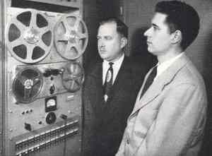 Two men looking at a 1950's computer