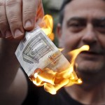 Anti-austerity protesters burn a euro note during a demonstration outside the European Union offices in Athens, Greece