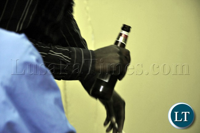 A soccer fan holds a bottle of Castle lager during the televising of the Zambia Bukina Faso match in Lusaka.