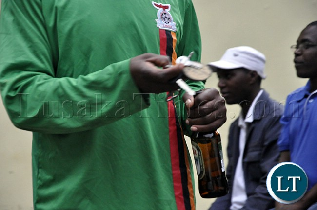 A soccer fan holds a bottle of Mosi lager during the Zambia Bukina Faso match in Lusaka