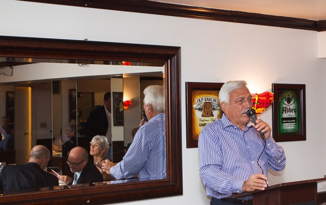 Kaegle stands with Casella, in front of one of the many wine art posters in this special downstairs dining room with bar.