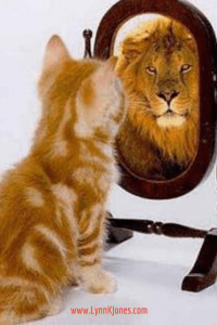 An orange pussy cat is looking at his reflection in the mirror and sees a lion