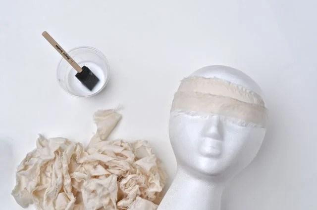 Glue the fabric onto the foam head for the DIY mummy