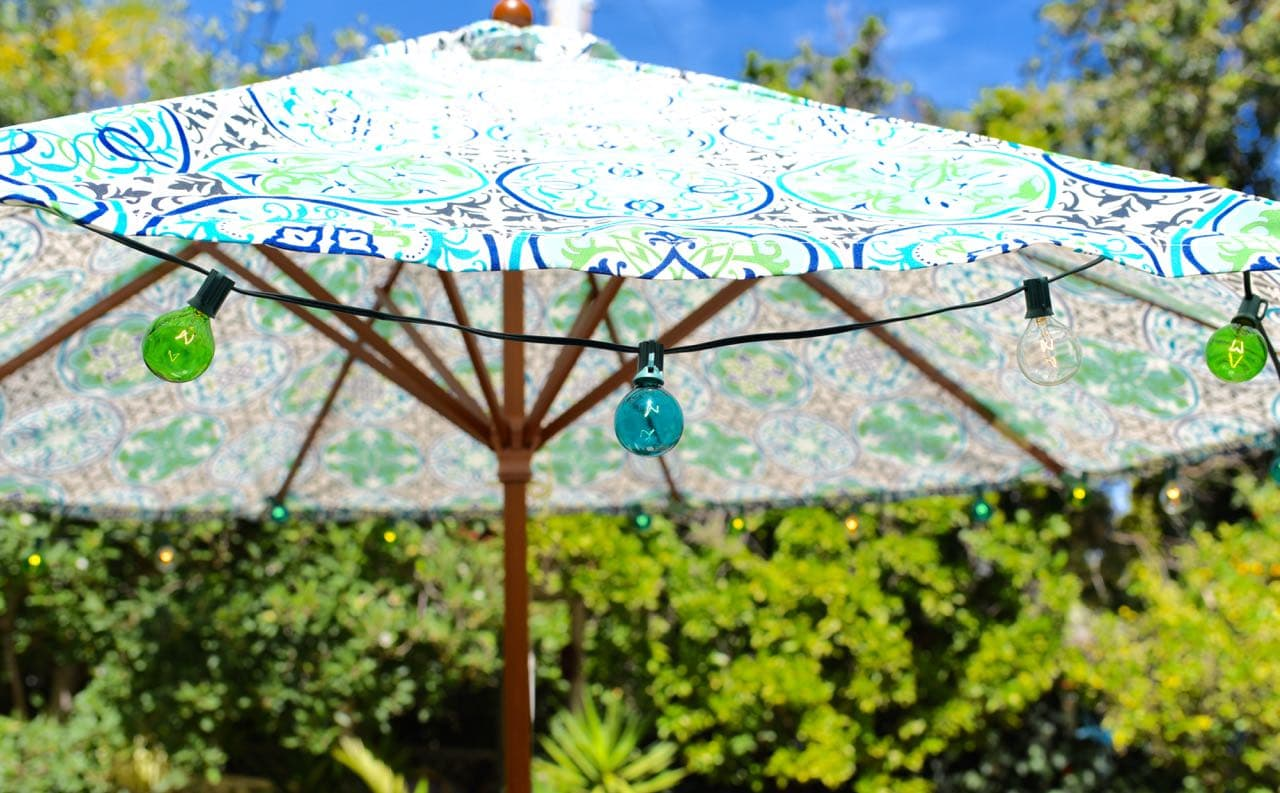Outdoor umbrella with string lights for Lesley Nicol's backyard makeover