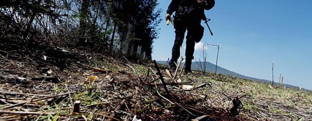 Un miembro de la policía estatal parado junto a una mancha de sangre durante una búsqueda de pruebas el 23 de mayo 2015, en un rancho ubicado en la carretera Jalisco-Michoacán en la región de Tanhuatose, Michoacán, México; donde 42 personas murieron a manos de las fuerzas de seguridad mexicanas. © 2015 Getty Images
