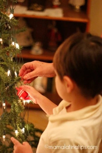 Niño-putting-up-Christmas-ornament