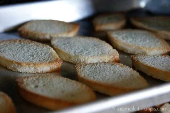 Toasting bread for bacon and bean crostinis