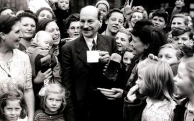 Den britiske statsministeren Clement Attlee gjennomførte en rekke strukturreformer, som nasjonalt eierskap over naturressurser og innføring av gratis helsetilbud for alle, i etterkrigstiden. Her drikker han te med velgere i Limehouse, London, i juli 1945, kort etter Labors' voldsomme valgseier det året. Foto: The spirit of 45.