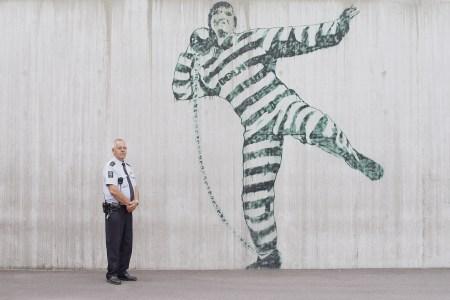 """Fengselsbetjent i Halden fengsel og en mann med fotlenke. Fra filmen """"Cathedrals of culture"""" av Wim Wenders. Foto: Filmweb"""