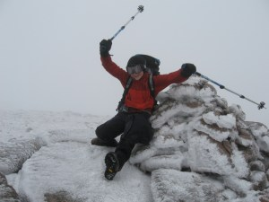 Alfie celebrating in the wind at the top of Cnap Coire na Spreidhe