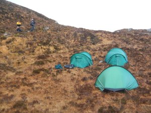 The tents pitched in a bog on the side of a hill