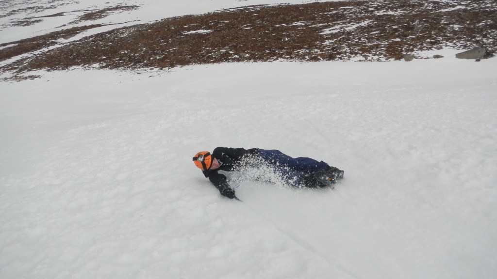 Using the ice axe to spin around and stop during a head first slide