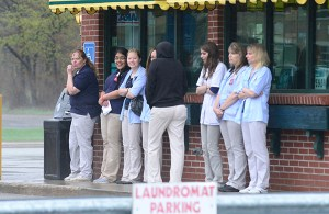 Rite Aid employees wait at the gas station across the street.