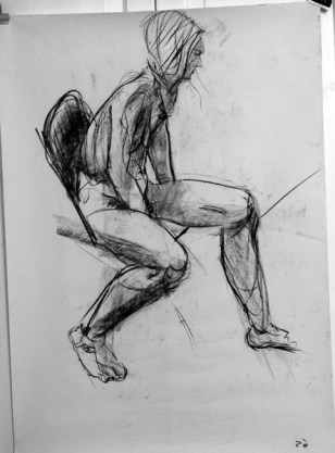 A charcoal life drawing of male model Andres, seated with one knee forward and one arm between his legs