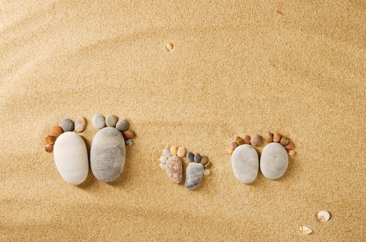 Stone arranged like three footprints on the beach