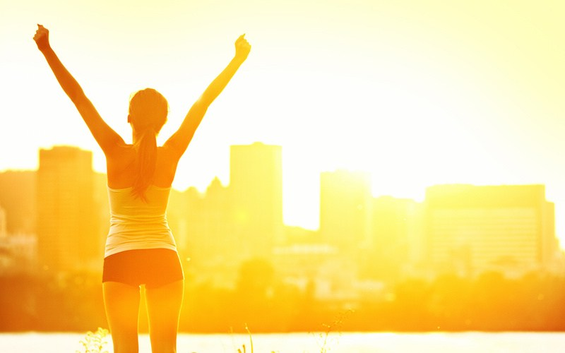 Success winner woman standing with arms up joyful after outdoors workout. Half silhouette on sunny warm summer day with city skyline in background, From Montreal, Quebec, Canada.