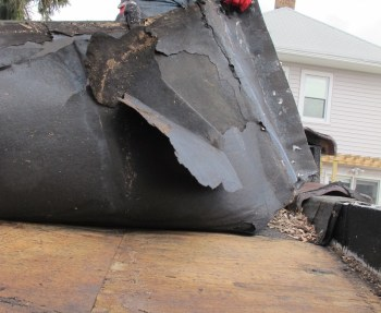 Tar paper damage caused by wind.
