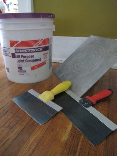 Prepping to begin filling holes in plaster with all purpose joint compound.