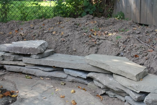 Preventing soil runoff onto our new patio with a small scrap flagstone wall.