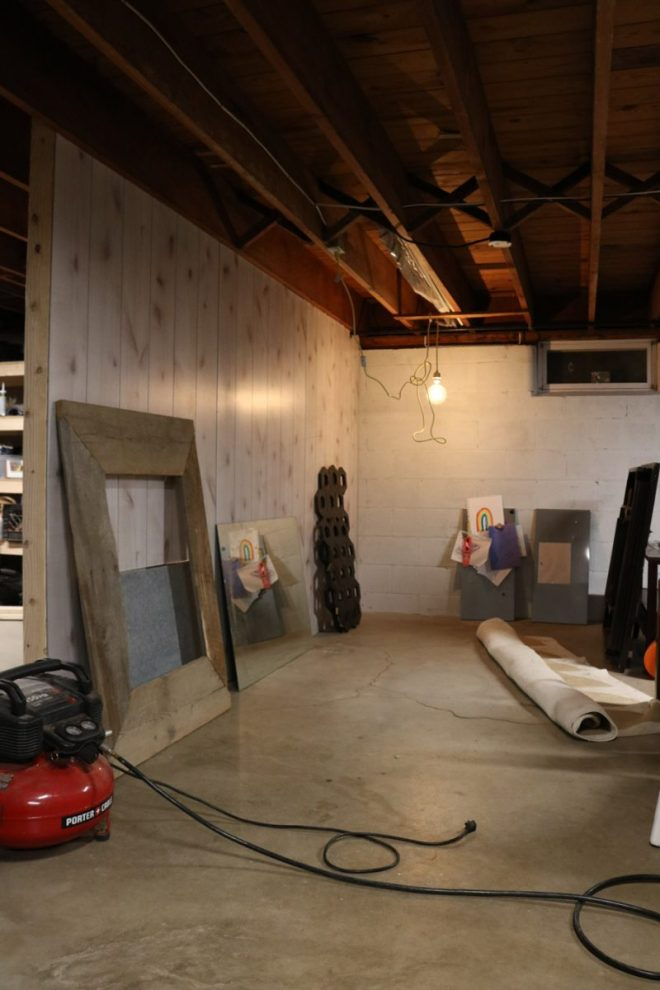 Primed and paneled walls in a basement art room.