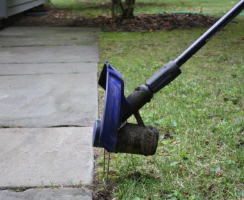 Using a string trimmer to edge a sidewalk for spring maintenance.