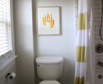 Our remodeled bathroom with light gray walls and accents in bright yellow.