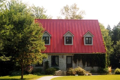 This fieldstone cottage in Ontario combines elements of the old and new with traditional stone walls and a bright red steel roof from Metal Roof Outlet.
