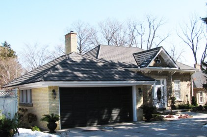 This yellow brick cottage in Ontario features a beautiful slate-style roof from Metal Roof Outlet.