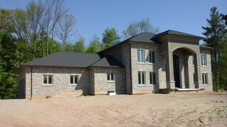 This grand fieldstone house in Ontario chose a gorgeous, durable Steel Shingle from Metal Roof Outlet in the colour Onyx.