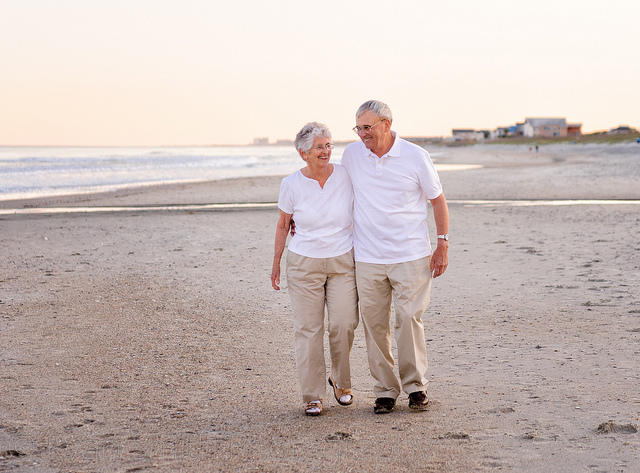 Grandparents walking down the beach together