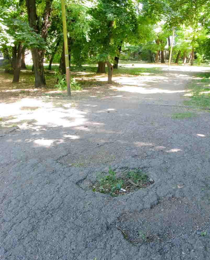 Holes in the park footpath, Taganrog - war graves.
