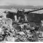 1941-01-23. TOBRUK - AN ITALIAN NAVAL GUN COMPLETE WITH GUNNER, SUFFERED ANOTHER DIRECT HIT FROM OUR ARTILLERY WHO ARE HAVING PLENTY OF PRACTICE.