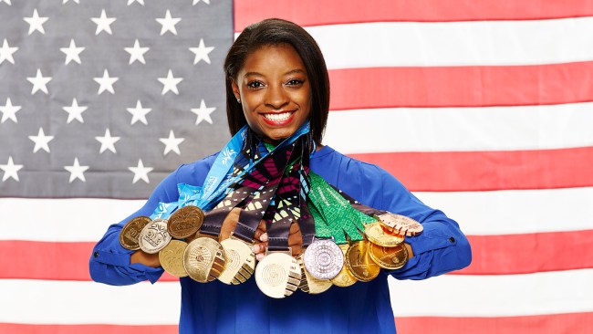 Simone Biles holding all of her medals
