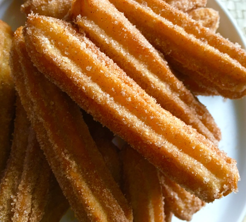 Roll the freshly fried churros in cinnamon sugar.