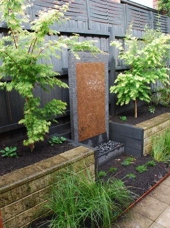 water wall garden design ideas evergreen plants trees stone wall garden privacy fence