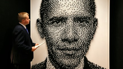 A Christie's employee looks at a portrait of Barack Obama by artist Joe Black called 'Shoot to Kill' made from thousands of plastic toy soldiers, during a press preview at Christie's auction rooms in London, Monday, Aug. 3, 2015. (AP Photo/Kirsty Wigglesworth)