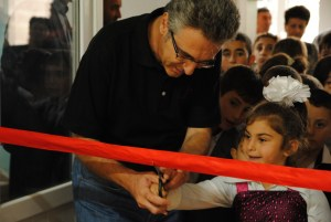 Sevan Amirians of Paros gets help from excited children in the ribbon-cutting.