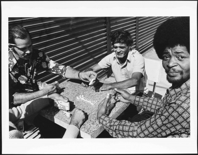 Photo: The daily domino game in front of the Social Club. 1976-1982. Gelatin silver print. Museum of the City of New York, Gift of Roberta Perrymapp, 2013.12.28. © Mel Rosenthal.