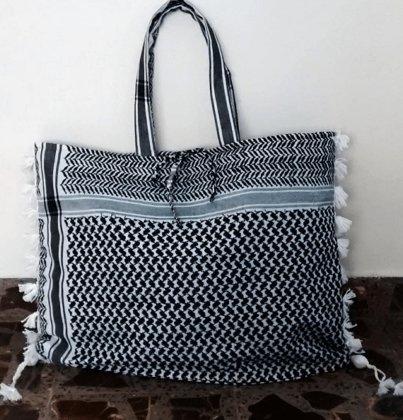 SchermKeffiyeh bag handmade by the skilled hands of woman from disadvantaged communities in Jordan. By Tribalogy Color: Black Size 60x47x15 cm Inside lining green/turqoise Extra inside bag with zipper
