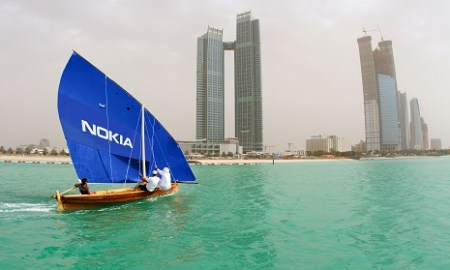 Arab man in a wooden sailing boat sails in front of the skyline of Abu Dhabi, Emirate of Abu Dhabi, United Arab Emirates