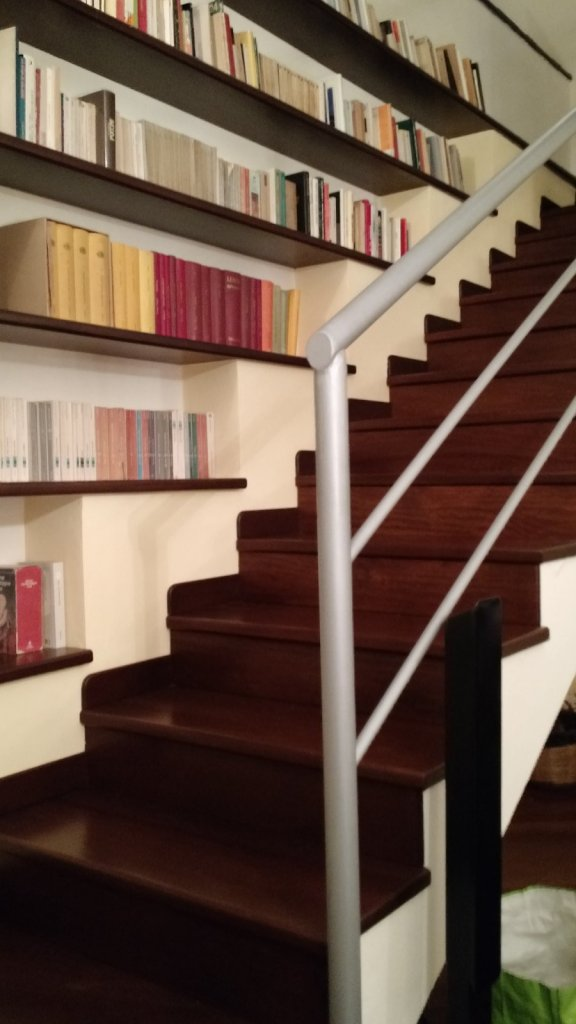 Book case and stairs to the left of the entrance to the living room.