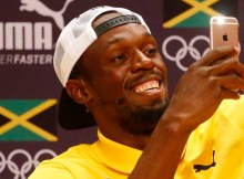 2016 Rio Olympics - Athletics - Rio de Janeiro, Brazil - 08/08/2016. Usain Bolt uses an Apple iPhone while giving a press conference. REUTERS/Nacho Doce - RTSLZJI