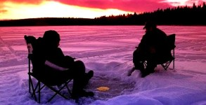 Saskatchewan_two_people_ice_fishing_on_McPhee_Lake_at_dusk_with_dark_red_sunset_in_background_722299