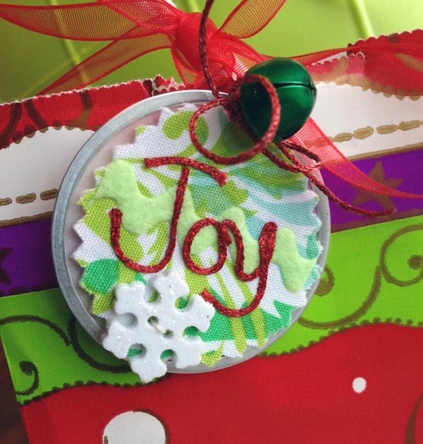 "Kreinik Iron-on Metallic Threads ""write"" the word Joy on this recycled gift tag."