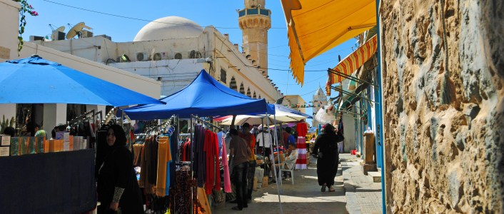 Stalls of street vendors are pictured in the old town of Tripoli, Libya, 8 June 2013. In this area of the Souq, clothing is offered so that it is mostly Libyan women who are the customers buying clothes for their families. In the background, the minaret of the Ahmad Pasha Qaramanli mosque can be seen. Photo by: Matthias Tödt/picture-alliance/dpa/AP Images