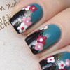 Floral nail art on teal and black