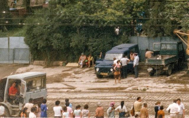 Masina Aro cu numere galbene, inconjurata de militieni si securisti, precum si o parte din multimea prezenta.