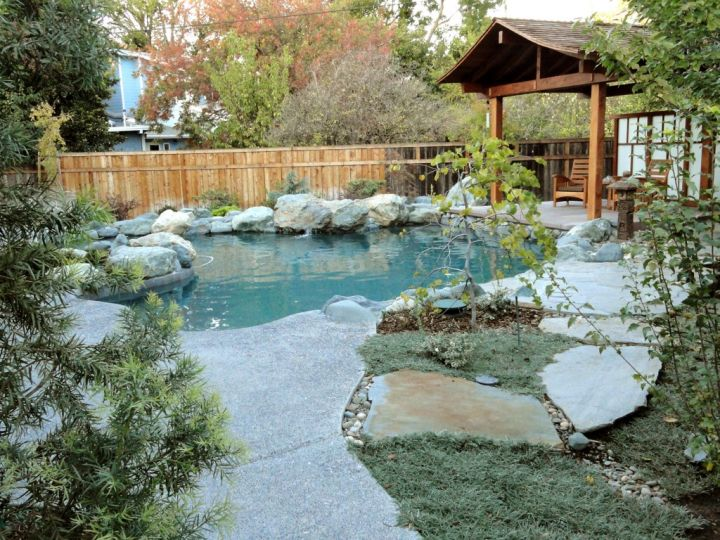 Rustic japanese style backyard with pergola and koi pond for Koi pond next to pool