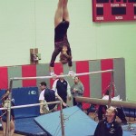 Naugatuck's Kassie Merancy, spotted by Pomperaug coach Hal Rettstadt, performs on the uneven bars during last Thursday's informal NVL championships. Merancy won the event with a score of 8.75 and the all-around title.